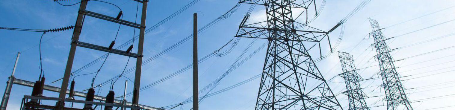 Strommasten bei Nacht an einer Autobahn